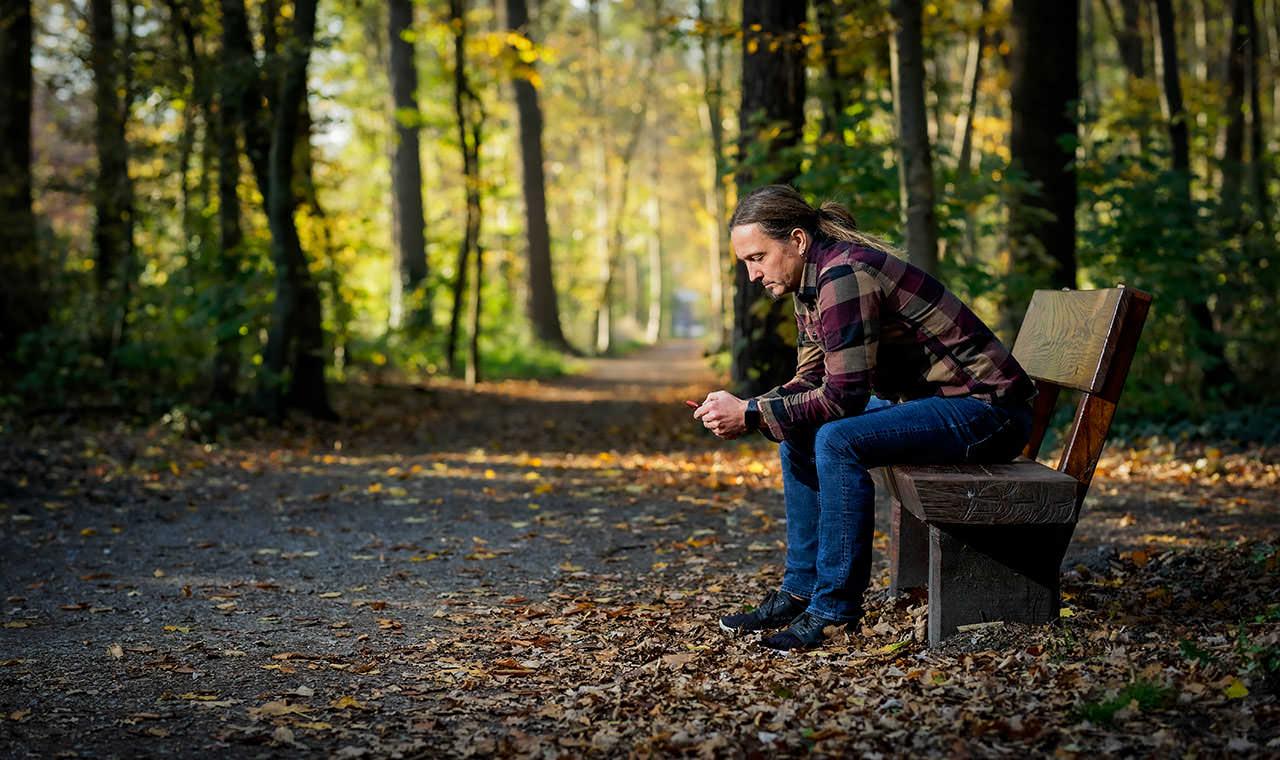 Ein Foto auf dem ich im Wal auf einer Bank sitze und auf mein Mobiltelefon schaue